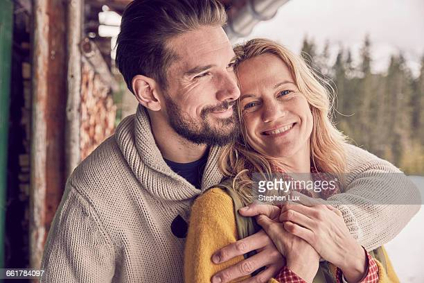 portrait of romantic couple standing outside log cabin in winter, elmau, bavaria, germany - cougar woman fotografías e imágenes de stock