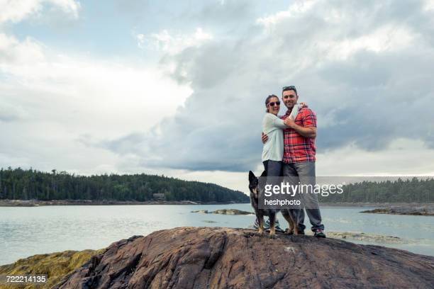 portrait of romantic mid adult couple and dog on rock at coast of maine, usa - heshphoto stock pictures, royalty-free photos & images