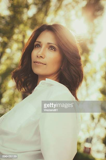Portrait of romantic woman with brown hair standing at backlight
