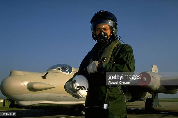 Portrait of Rory Underwood the England Winger and RAF Pilot in full flying gear holding a rugby ball and standing next to an aeroplane at RAF...