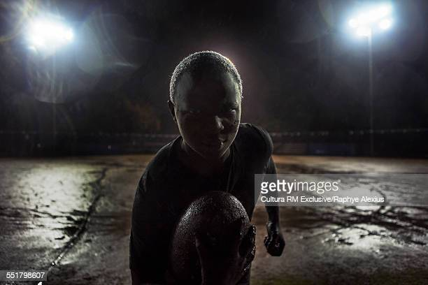 Portrait of rugby player with ball on field