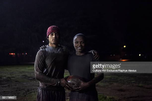 Portrait of rugby players with ball on field