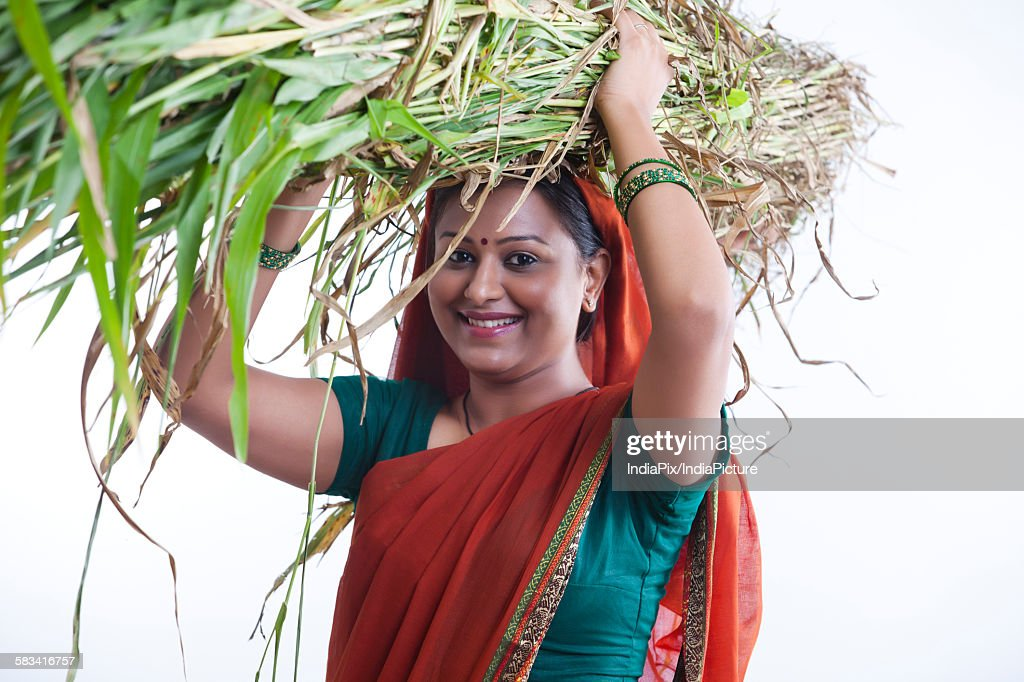 Portrait of rural woman carrying fodder : Stock Photo