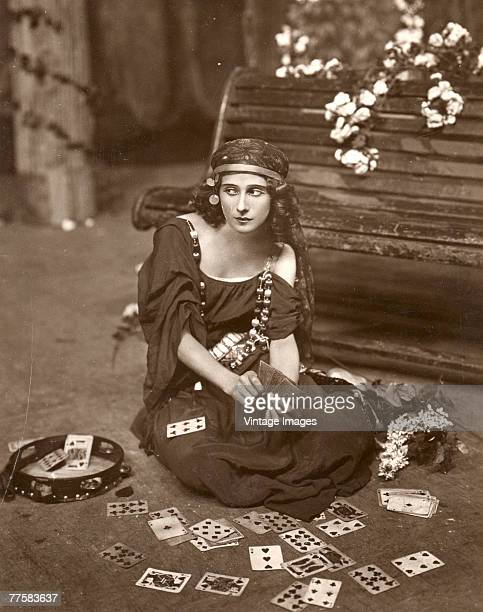 Portrait of Russian ballet dancer Anna Pavlova as she sits on the floor in front of a bench in costume and surrounded by playing cards a tambourine...