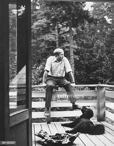 Portrait of Russian poet Yevgeny Yevtushenko relaxing on the balcony of a country house with his dog 'Datcha' January 15th 1973