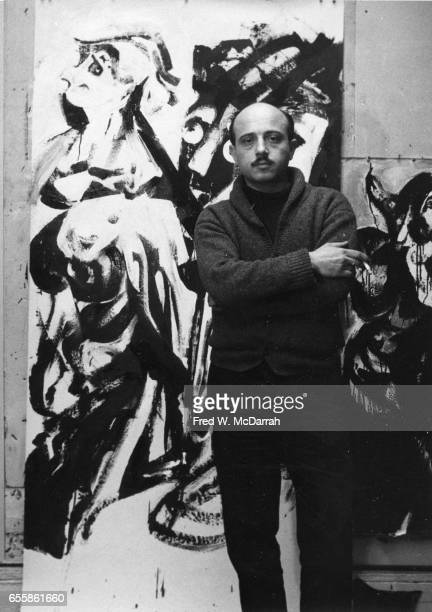 Portrait of Russianborn American artist Boris Lurie a cigarette in his hand as he poses in front of one of his paintings at the March Gallery New...