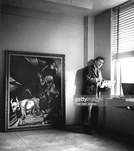 Portrait of Russian-born French artist Marc Chagall as he stands next to one of his paintings beside a window, 1941.