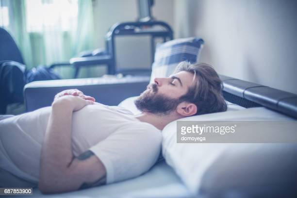 Portrait of sad bearded man lying down in the bad