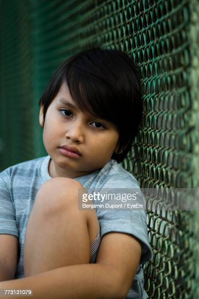 portrait of sad boy leaning on chainlink fence - one boy only stock pictures, royalty-free photos & images