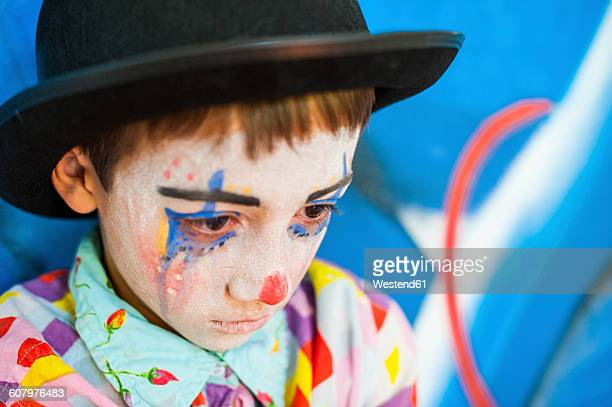 portrait of sad boy rouged as a clown - sad clown stock photos and pictures