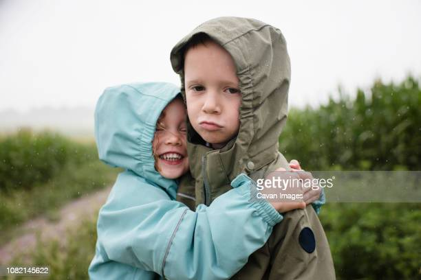 Portrait of sad brother being embraced by happy sister while standing against plants during rainy season