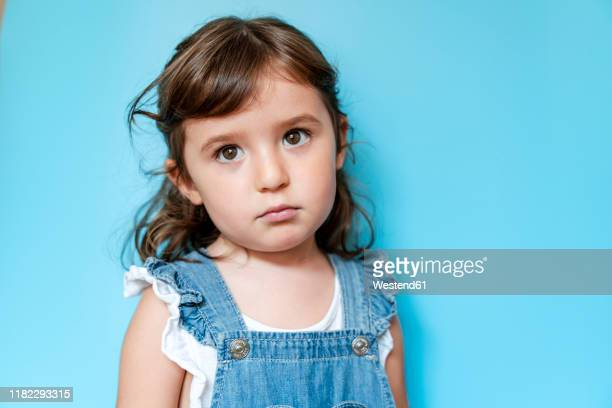portrait of sad girl, blue background - sad child stock pictures, royalty-free photos & images
