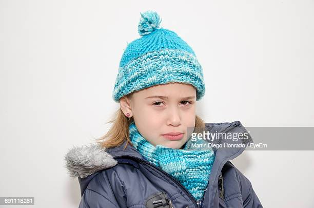 Portrait Of Sad Girl In Warm Clothes Against White Background