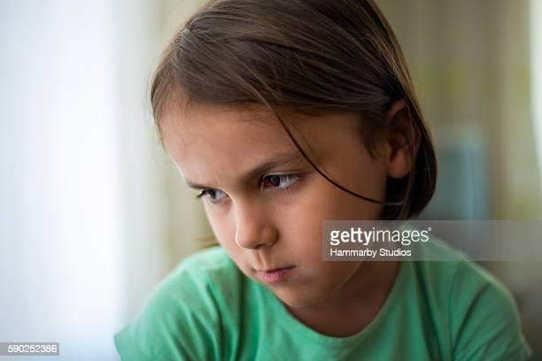 Portrait of sad girl looking away next to window