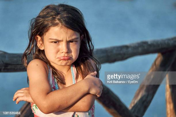 portrait of sad girl standing against railing - puckering stock pictures, royalty-free photos & images