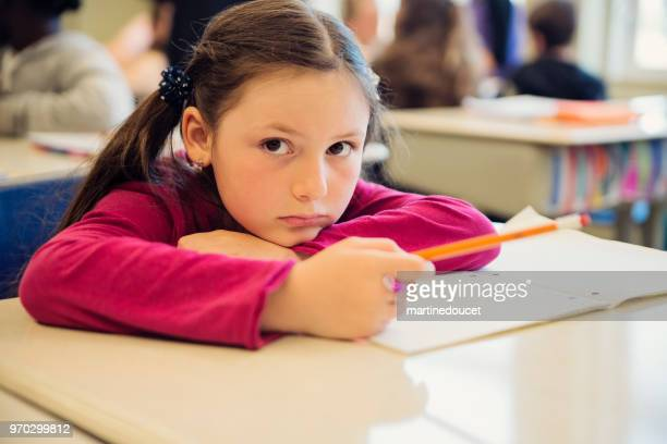 Portrait of sad little girl in classroom, sitting at her desk.