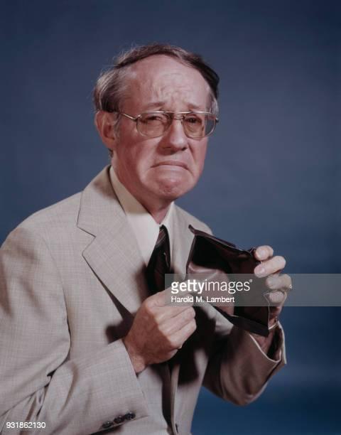 Portrait of sad man showing empty wallet