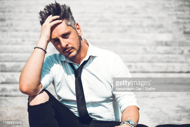 portrait of sad man with hand in hair sitting on steps - 髪に手をやる ストックフォトと画像