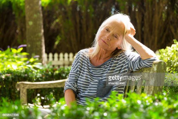 Portrait of sad, modern, attractive mature woman in sunshine