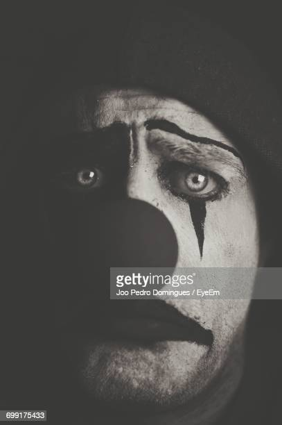 portrait of sad pierrot against black background - sad clown stock photos and pictures