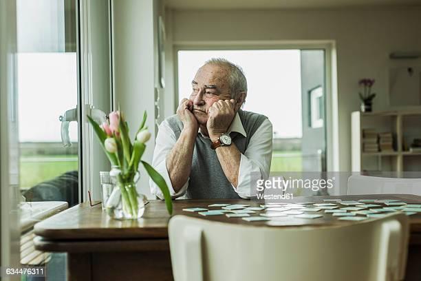 portrait of sad senior man looking through window - einsamkeit stock-fotos und bilder