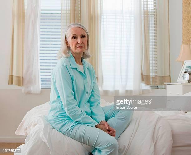 Portrait of sad senior woman sitting on bed wearing pyjamas