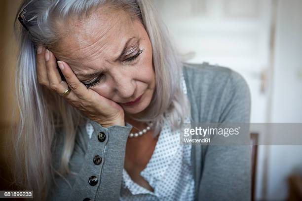 Portrait of sad woman with head in her hand at home