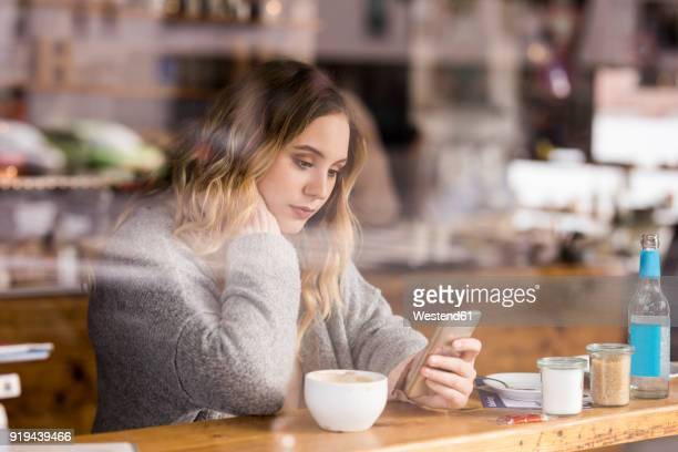 portrait of sad young woman in a coffee shop looking at cell phone - 悲しみ ストックフォトと画像