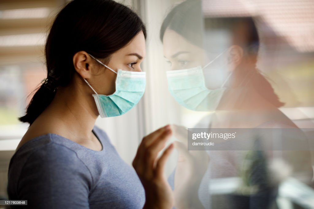 Portrait of sad young woman with face protective mask looking through the window at home : Stock Photo