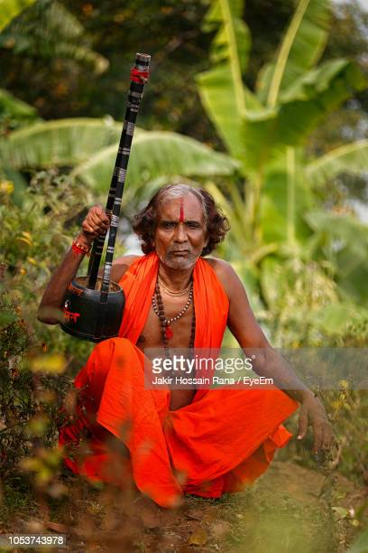 portrait of sadhu crouching on field - bangladeshi culture stock pictures, royalty-free photos & images