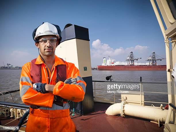 portrait of sailor in protective workwear on tugboat at sea - industrial ship stock pictures, royalty-free photos & images