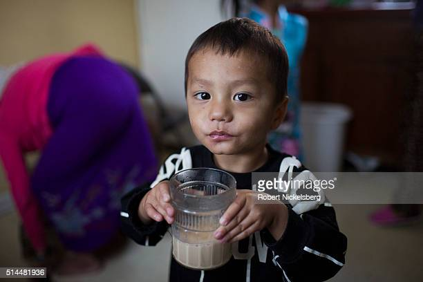 Portrait of Sajal Gurung as he holds a glass of tea in his uncle's apartment Burlington Vermont January 5 2016 Members of the extended Gurung family...