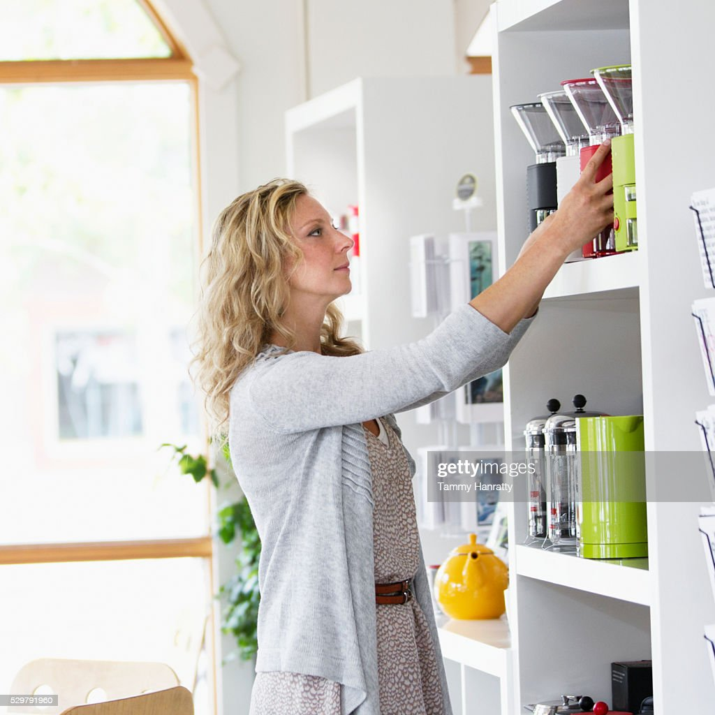 Portrait of sales clerk putting products on shelf : Stock Photo
