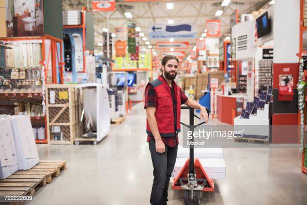 portrait of salesman standing by handtruck in hardware store - jacket stock pictures, royalty-free photos & images