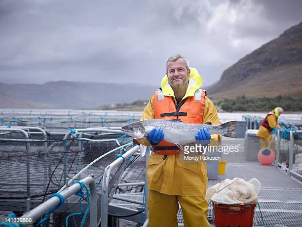 Portrait of salmon farmer holding hand reared Scottish salmon on farm pontoon on sea loch
