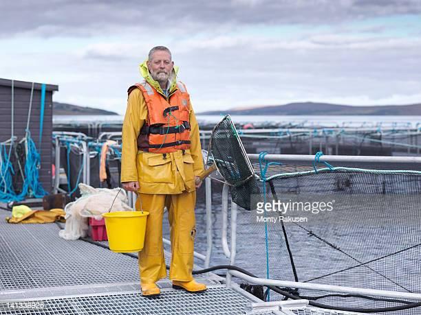 portrait of salmon farmer standing on pier of scottish salmon farm - monty rakusen stock pictures, royalty-free photos & images