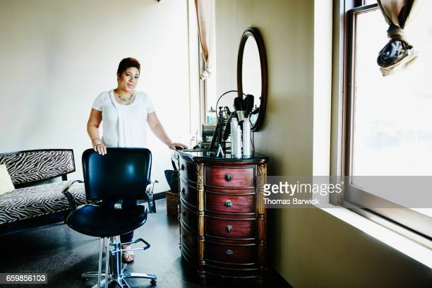 portrait of salon owner standing in workstation - 美容室 椅子 ストックフォトと画像