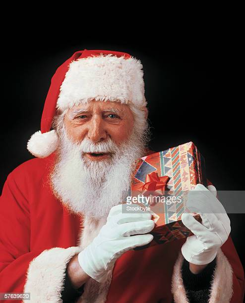 portrait of Santa Claus holding Christmas gift