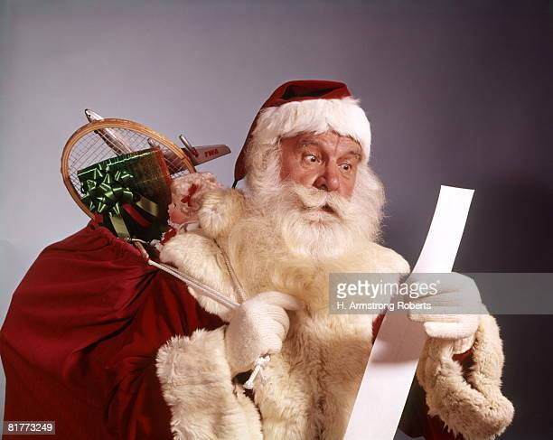 portrait of santa claus holding sack filled with toys and checking his list naughty nice tradition. - santa face stockfoto's en -beelden