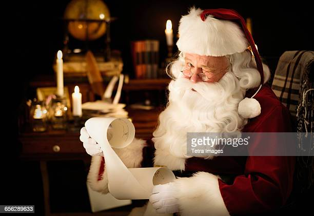 portrait of santa claus reading childs letter and winking - naughty santa stock photos and pictures