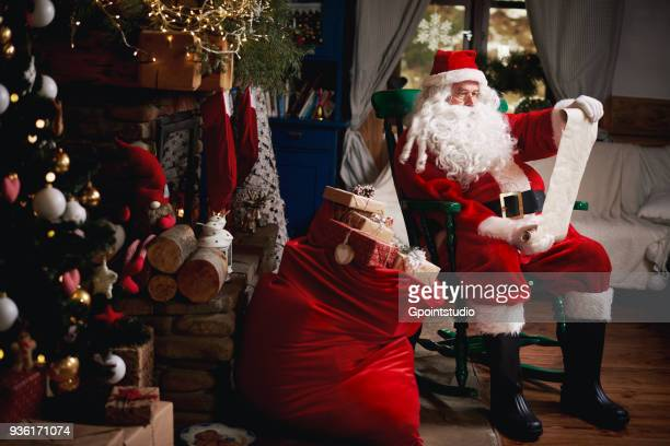 portrait of santa claus, sitting in chair with sack full of presents, looking at christmas list - santa claus fotografías e imágenes de stock