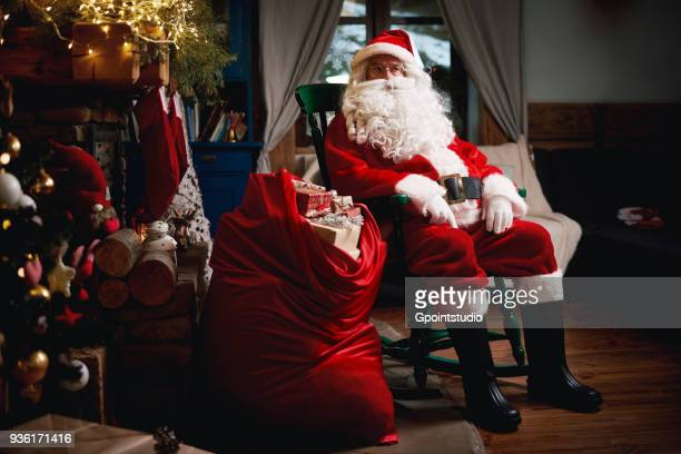 portrait of santa claus, sitting in chair with sack full of presents - grotto stock pictures, royalty-free photos & images