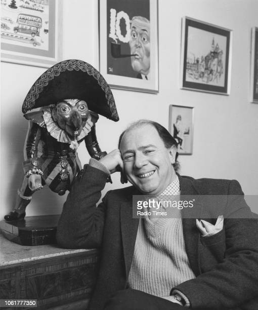 Portrait of satirist Alan Coren editor of 'Punch' magazine with a statue of the character 'Punch' February 1983