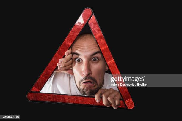 Portrait Of Scared Mid Adult Man Looking Through Reflector Against Black Background