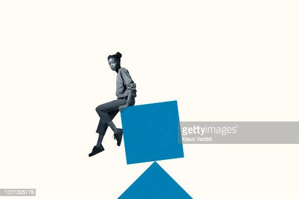 portrait of scared woman sitting on blue block - quadrato composizione foto e immagini stock