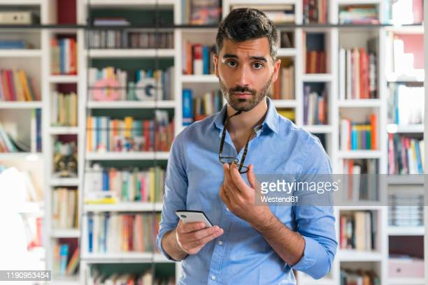 portrait of sceptical young man with smartphone standing in front of bookshelves - 眉を上げる ストックフォトと画像
