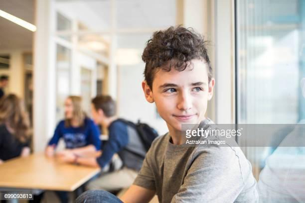 Portrait of schoolboy (12-13) looking through window