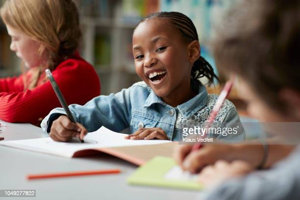 portrait of schoolgirl drawing at the school library and laughing - primary school child stock pictures, royalty-free photos & images