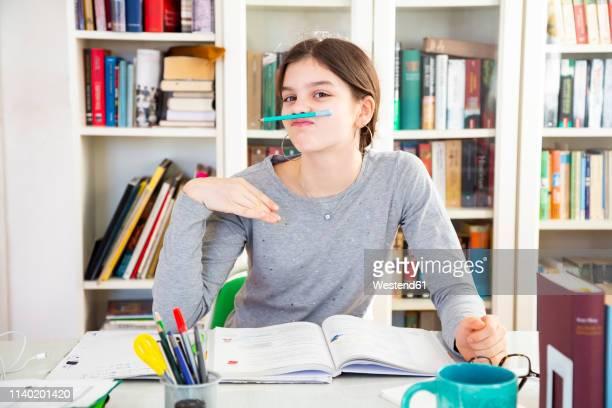 portrait of schoolgirl making faces - schulbuch stock-fotos und bilder