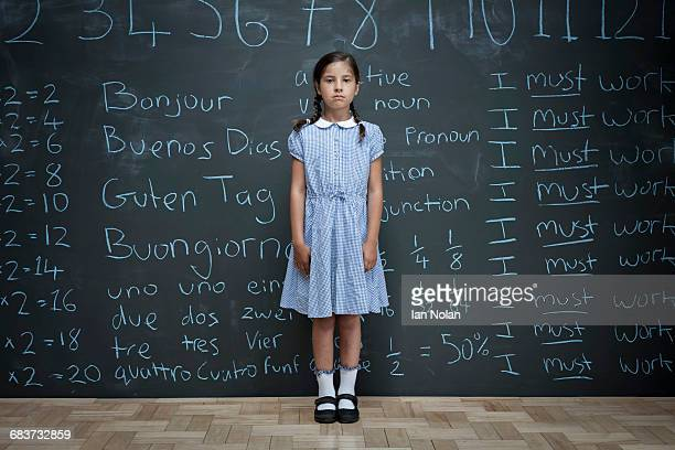 portrait of schoolgirl standing in front of large chalkboard with schoolwork chalked on it - schoolgirl stock pictures, royalty-free photos & images